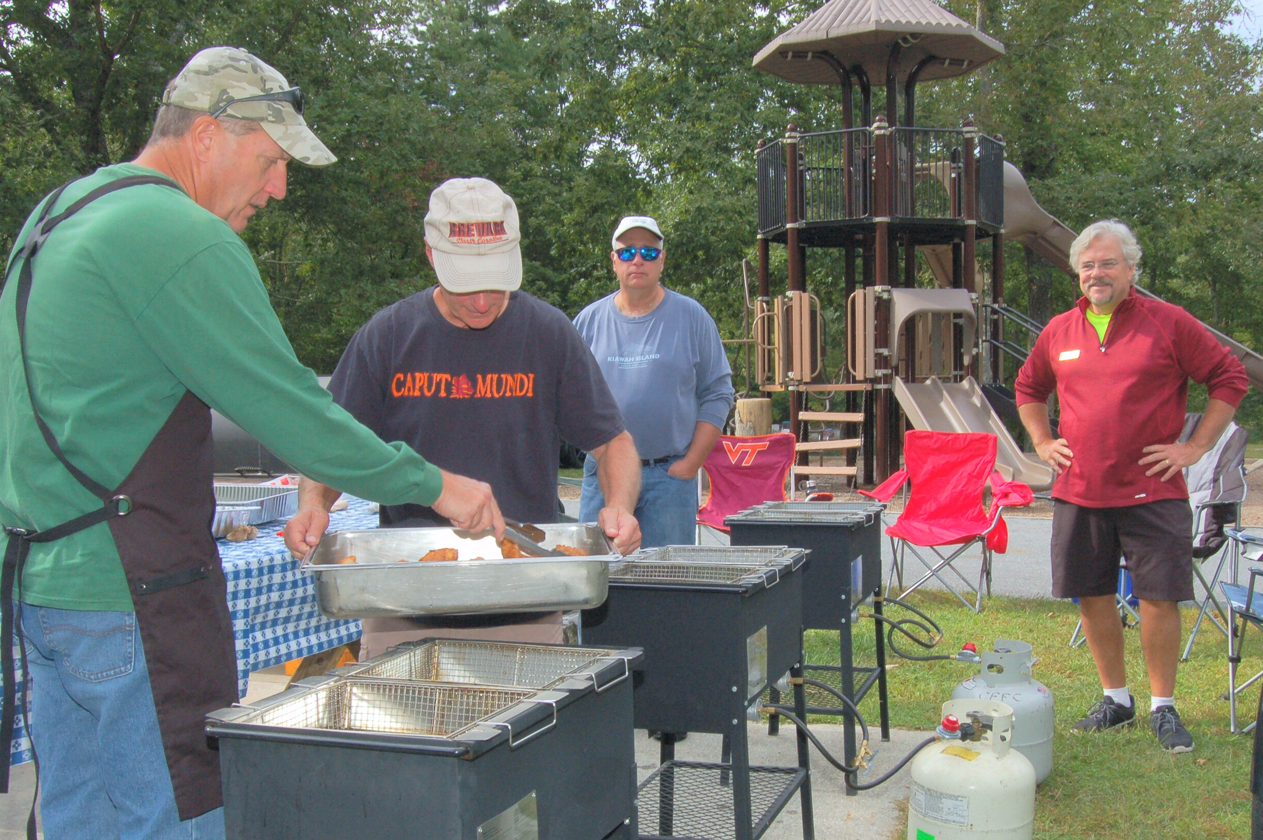 Club President Jim Bailey watches Joe Mihelcic, T.J. Kopt and Mike Huckabey deep fry some 200 catfish filets.