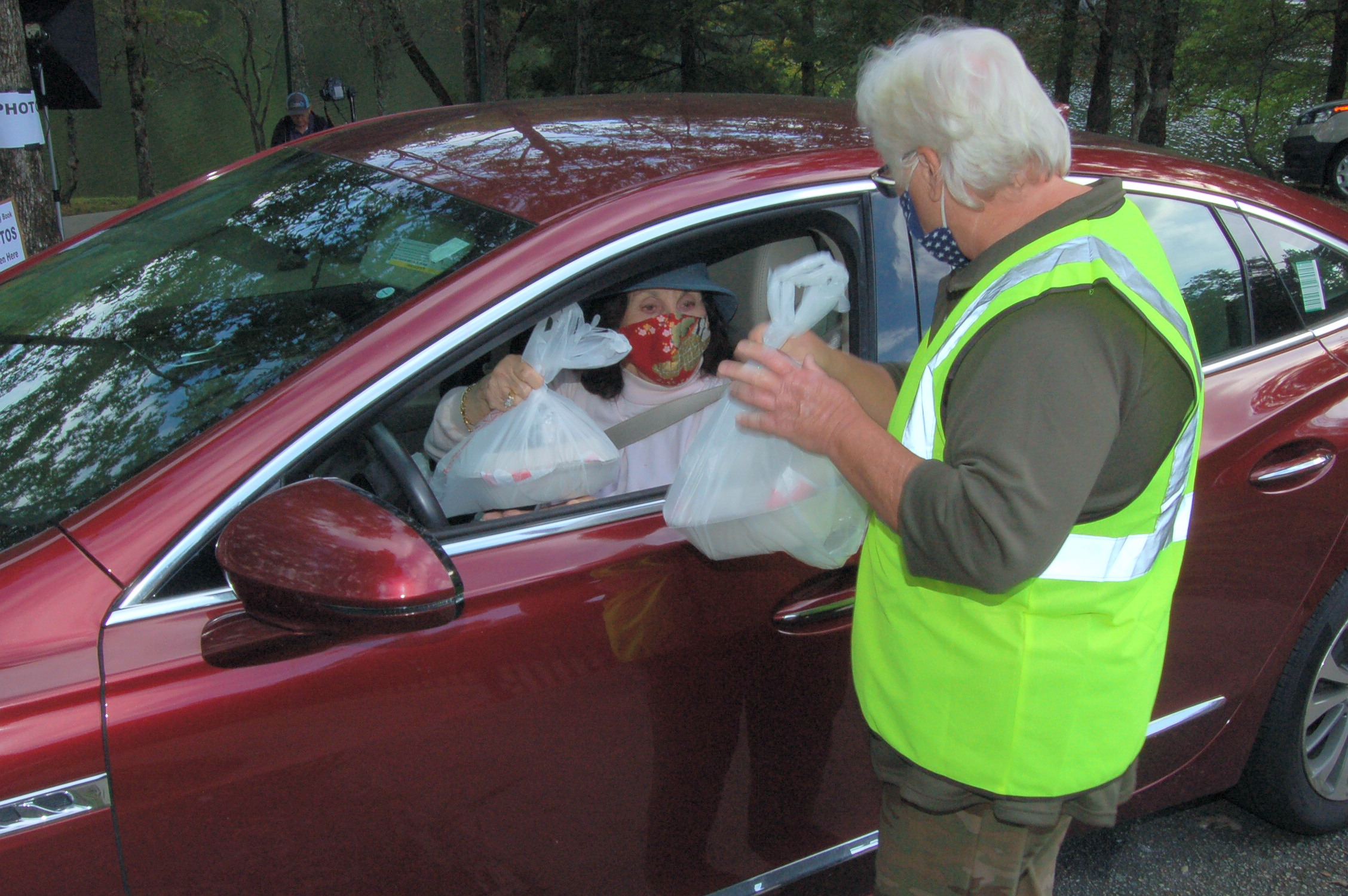 Volunteer Lori Foradori hands out dinner bags to Ann Strother